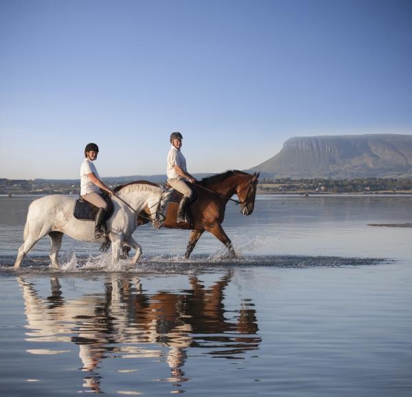 Couple riding horses in the sea Sligo Ireland by Horse photographer Ireland Professional Ni Riain Fine Art Equine Photography